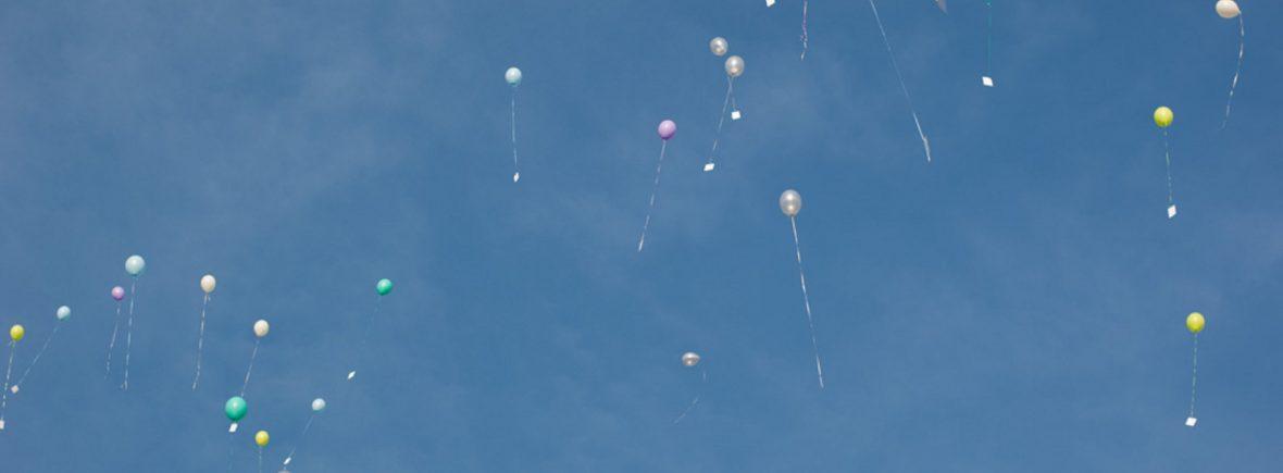 Kontakt. Blauer Himmel mit bunten Luftballons and denen Postkarten davonfliegen.